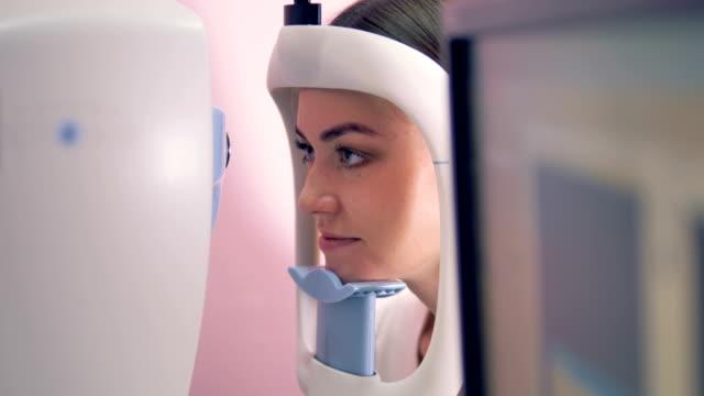 nahaufnahme von gesicht einer jungen frau während ihrer sehkraft-prüfung - augenheilkunde stock-videos und b-roll-filmmaterial