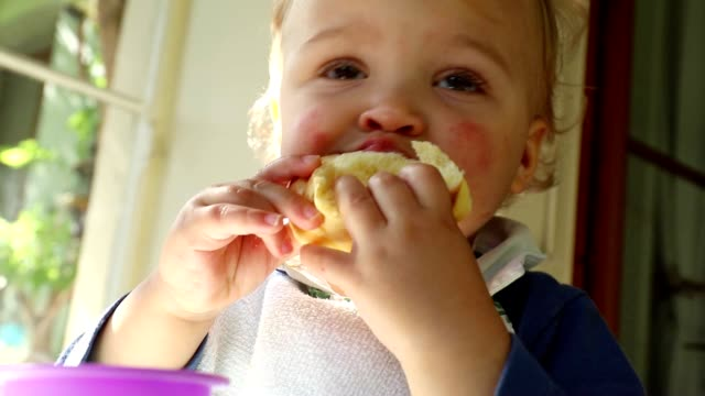 Close up of adorable cute baby toddler blonde boy on high chair. Portrait of baby eating cake and playing with baby toys Close up of adorable cute baby toddler blonde boy on high chair. Portrait of baby eating cake and playing with baby toys charming stock videos & royalty-free footage