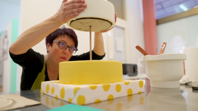 vidéos et rushes de fermez-vous vers le haut de la femme adulte faisant un gâteau de couche - boulanger