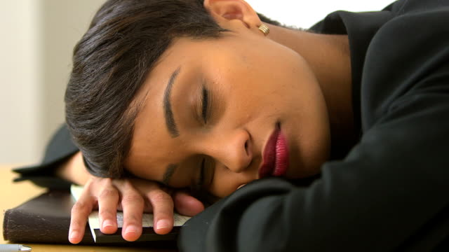 Close up of African American business woman sleeping in office video