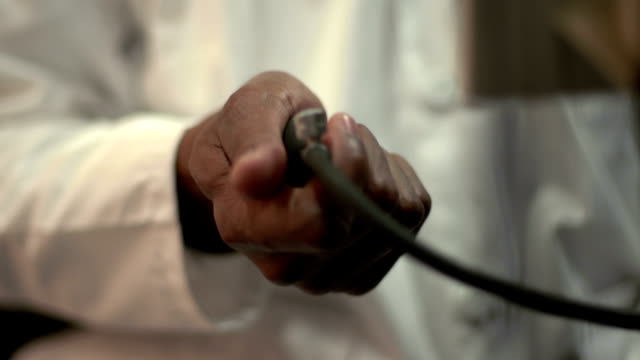 Close up of African American doctor measuring blood pressure Close up of African American Doctor's hands using a sphygmomanometer to measure blood pressure blood pressure gauge stock videos & royalty-free footage