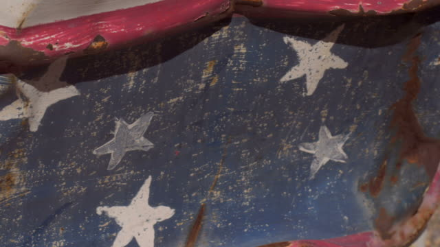 Close up of American Flag painted on a dented rusty metal trash can dolly shot