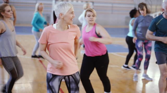nahe einer aktiven seniorin tanzt im fitnessstudio - aktivitäten und sport stock-videos und b-roll-filmmaterial