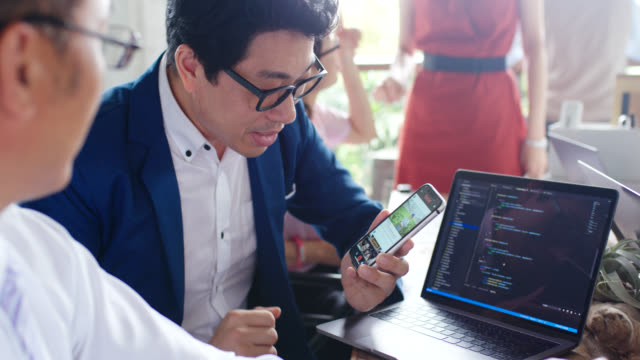 close up of an app developer demoing his social media app on a mobile phone and explaining it to a colleague - web designer video stock e b–roll