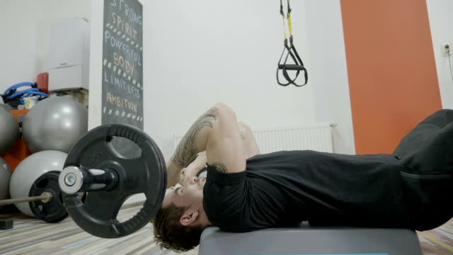 Close up of an attractive beautiful man lifting up weights in a gym while lying on a bench press video