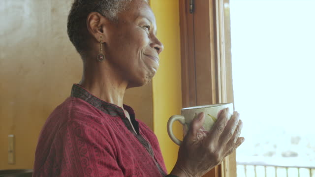 Close up of an attractive black senior woman smiling holding a coffee cup