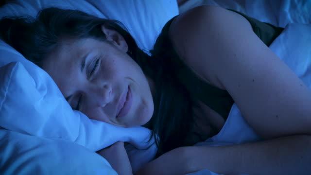 vídeos y material grabado en eventos de stock de cerca de una mujer atractiva sonriendo mientras duerme en la noche - dormir