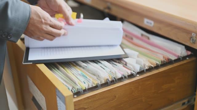 närbild av en officer söker dokument i lådan - looking inside inside cabinet bildbanksvideor och videomaterial från bakom kulisserna