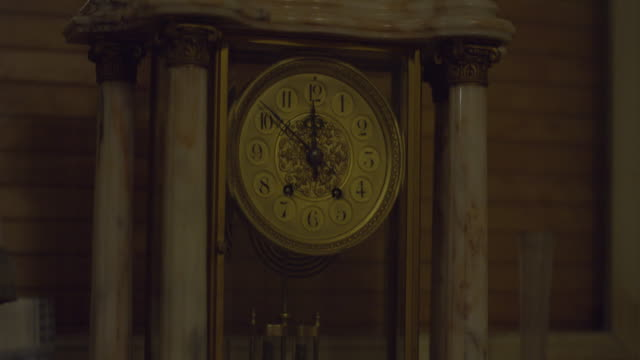 Close up of an old marble clock with a black lion sculpture in a creepy haunted house on a winter night. Tilt up. Halloween scary ambiance. Ghost, Demon or Spirit. Shot on RED SCARLET 6K.