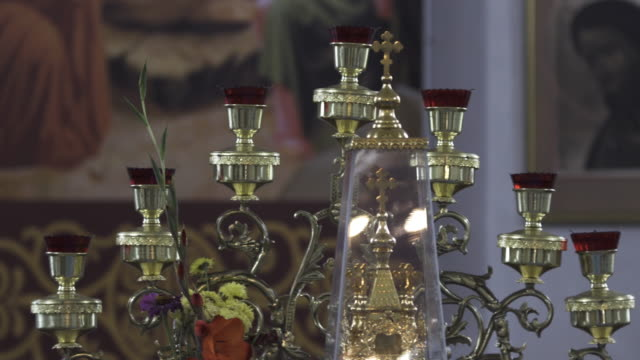 Close up of an old menorah in church. Stock footage. Details of interior inside of orthodox temple, beautiful candlestick with a cross and flowers on blurred icons background
