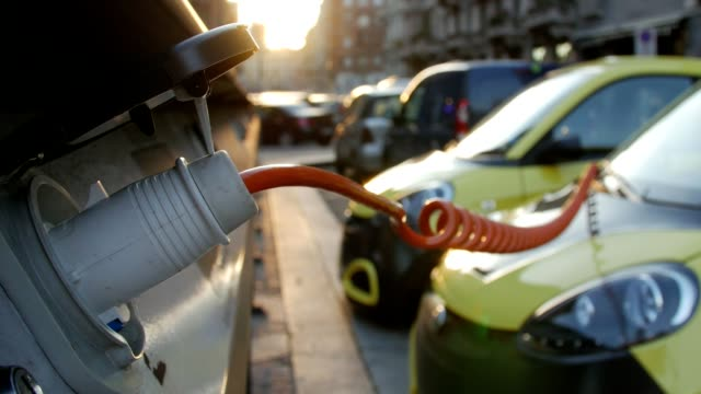vídeos de stock e filmes b-roll de close up of an yellow electric vehicle's plugged in charge port - green city
