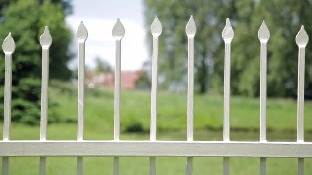 Close up of antique wrought iron fence outdoors in the park. Shallow depth of field, spikes on fence