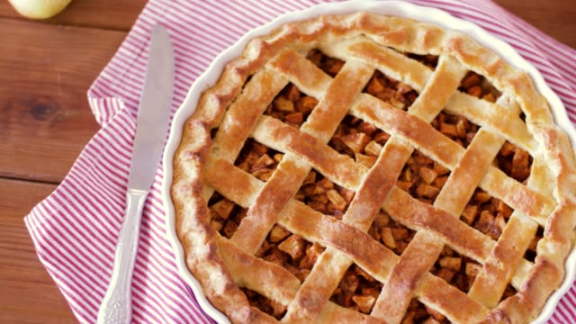 close up of apple pie and knife on wooden table