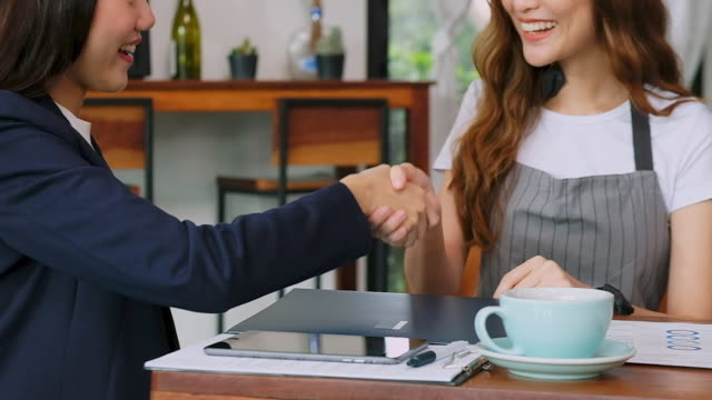Close up of asian business woman handshake with cafe owner before giving advice about financial planning for small business, slow motion