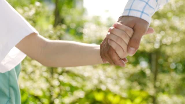 vídeos de stock, filmes e b-roll de close-up de asiático pai & filho mão & andando no jardim na manhã do - pai e filha