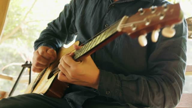 närbild av asiatiska man spelar gitarr på terrass för avkoppling aktivitet - akustisk gitarr bildbanksvideor och videomaterial från bakom kulisserna