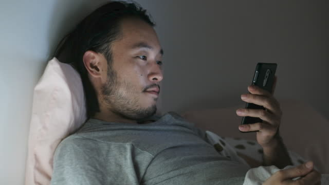 Video Close up of asian man struggle while using smart phone in bed at night