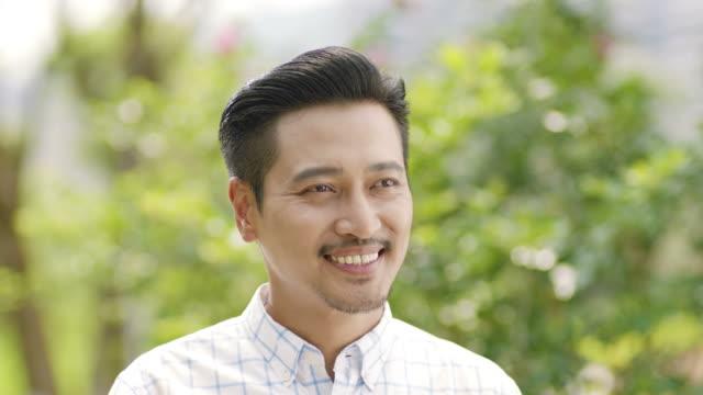 アジア人の男性の手を振って別れを笑顔のクローズ アップ - 男性 笑顔点の映像素材/bロール