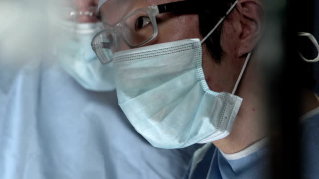 Close up of Asian surgeon working with assistant in surgery video