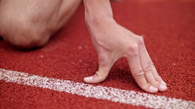 vidéos et rushes de fermez-vous vers le haut de la main d'athlète se préparant à la ligne de départ. - starting block