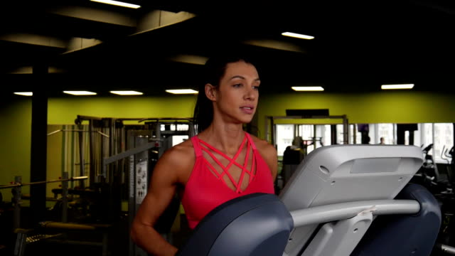 Close up of attractive mixed race woman running on the treadmill in the sport gym Close up of attractive mixed race woman running on the treadmill in the sport gym in slow motion. endurance stock videos & royalty-free footage