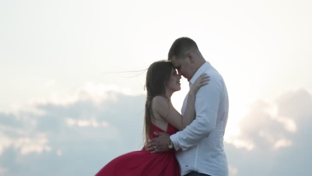 Close up of Attractive young couple kissing engaged in foreplay touching each other. Happy couple stands in embrace and kisses each other on beautiful sunset