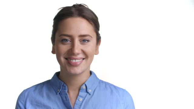 close up of attractive young woman smiling into camera - sfondo bianco video stock e b–roll