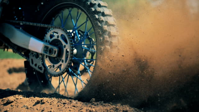 Close up of autobike's wheel starting motion and raising clouds of dust Close up of autobike's wheel starting motion and raising clouds of dust. HD motocross stock videos & royalty-free footage
