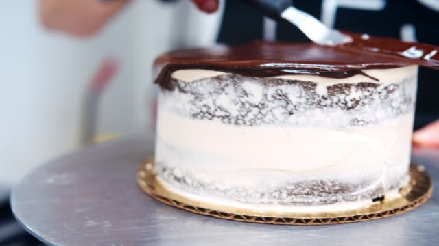 Close Up Of Baker Spreading Melted Chocolate On Cake With Knife