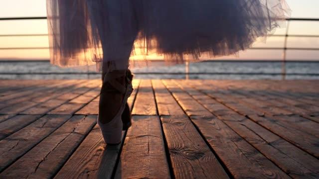 nahaufnahme von ballerina füße, erwärmung oben draußen auf dem bürgersteig nahe dem meer, zu fuß den zehenspitzen. sonne scheint vor dem hintergrund - ballettschuh stock-videos und b-roll-filmmaterial