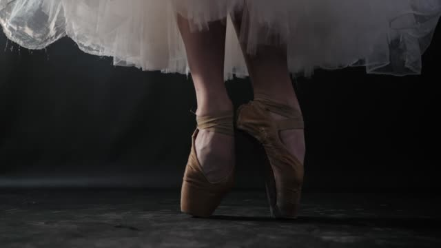 close up of ballet dancer as she practices exercises on dark stage or studio. woman's feet in pointe shoes. ballerina shows classic ballet pas. slow motion. flare, gimbal shot - danza classica video stock e b–roll