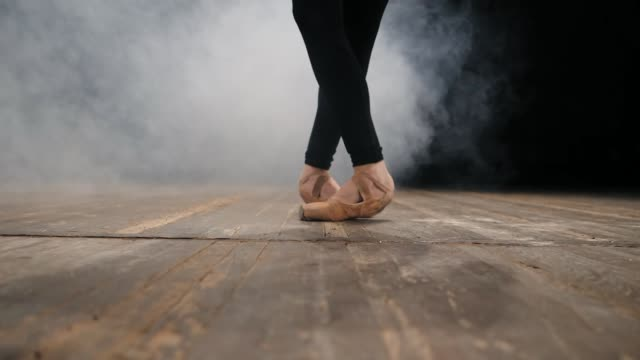 vidéos et rushes de gros plan des pieds du danseur de ballet en pointe réchauffé avant sur scène. pratiques de ballerine sur plancher en bois dans un studio sombre avec de la fumée. slow motion - tutu