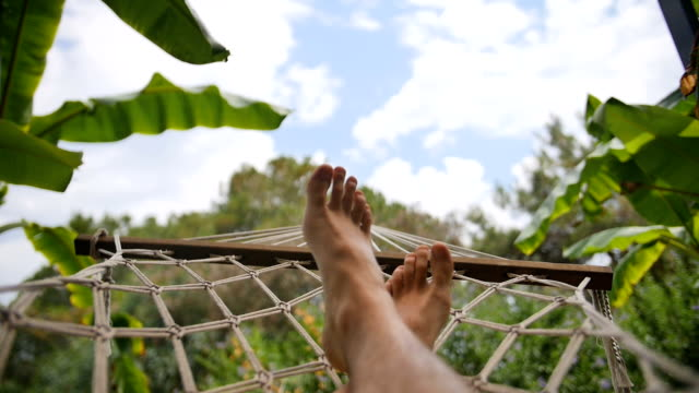 close up of bare feet of a man resting in a hammock on a sunny day. - amaca video stock e b–roll