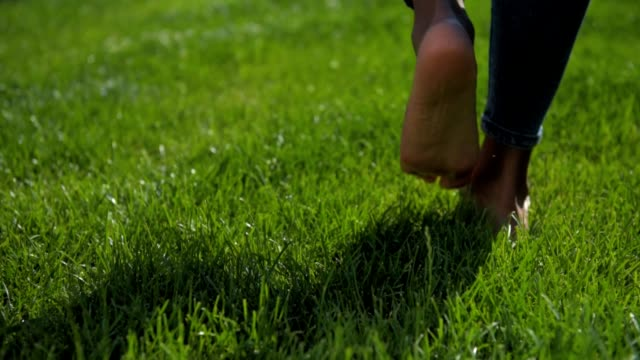 Close up of barefooted young girl walking on grass
