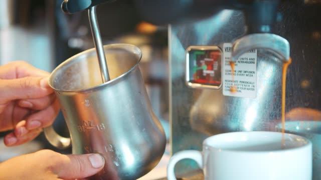 vídeos y material grabado en eventos de stock de close up de espumar la leche caliente para agregar al café barista - barista