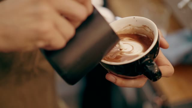 Close up of barista hand while making frothy drink of cocoa menu at the coffee shop for customer video