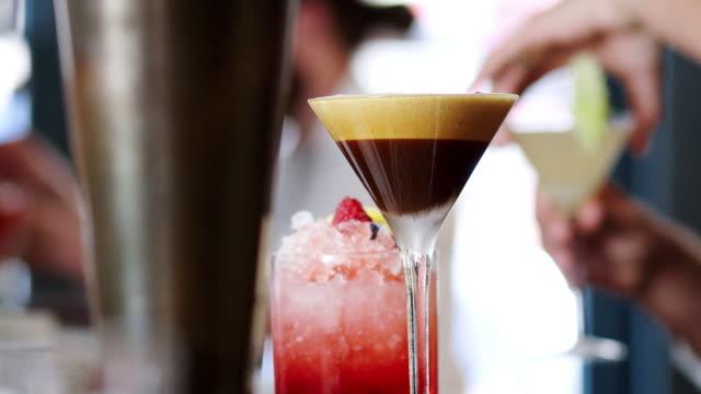 stockvideo's en b-roll-footage met sluiten van barman serveert espresso martini cocktail in bar - martini