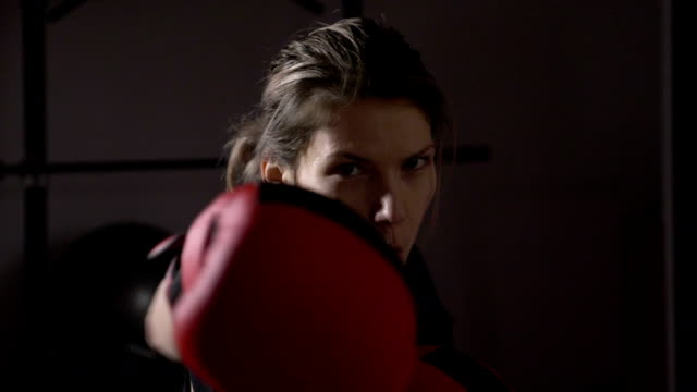 pov close up of beautiful female model looking into the camera and shadow boxing in slow motion - kick boxing video stock e b–roll