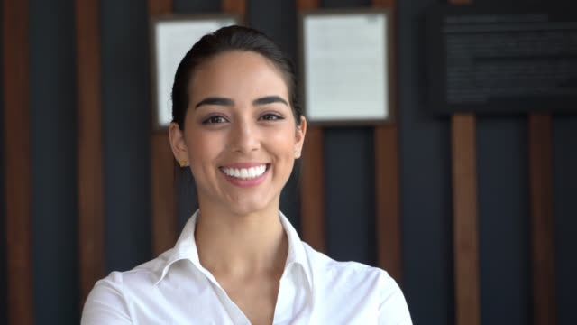 close up of beautiful latin american hotel receptionist facing camera smiling - direttrice video stock e b–roll