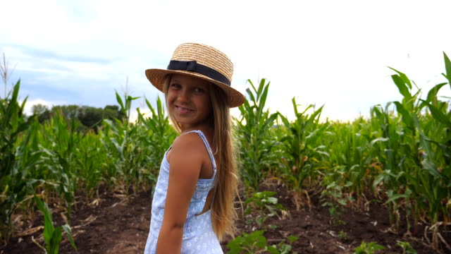 Close up of beautiful little girl in straw hat standing at corn field, turning to camera and smiling. Small kid with long blonde hair looking at maize plantation and enjoying nature landscape. Slow motion