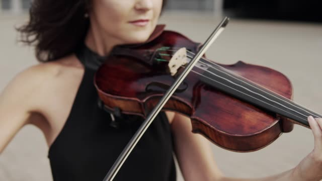 Close up of Beautiful violinist in black dress near glass building