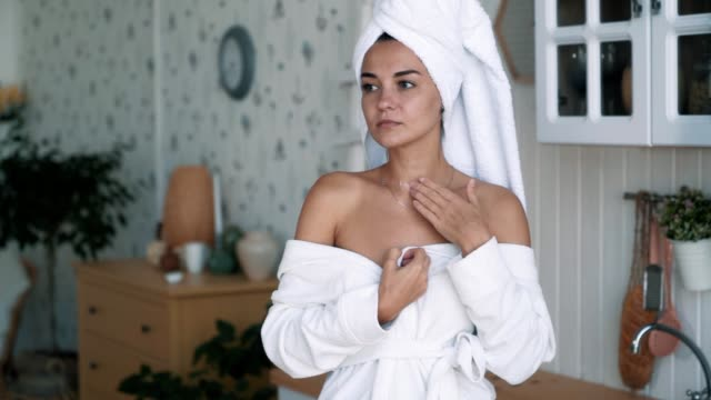 Close up of beautiful woman in bathrobe applies cream to neck, slow motion Close up of beautiful woman in bathrobe and with towel on head applies cream to neck, slow motion. Skin moisturizing, beauty products neck stock videos & royalty-free footage