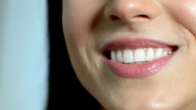 close up of beautiful woman smiling with perfect teeth - perfezione video stock e b–roll