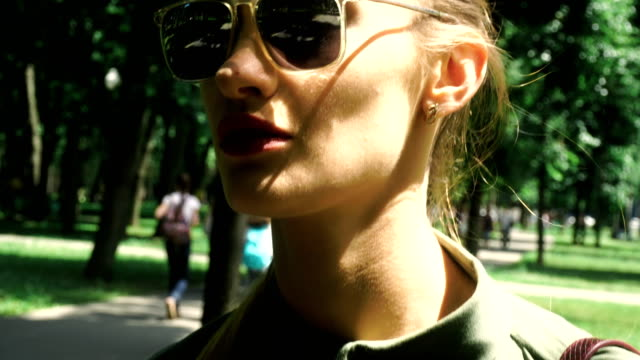 Close up of beautiful young lady in sumglasses with red lips walks outdoors video