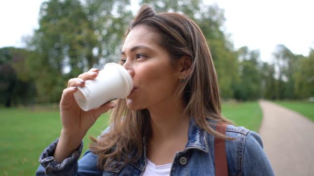 stockvideo's en b-roll-footage met close-up van mooie jonge vrouw in het park genieten van een take-out koffie - mid volwassen vrouw