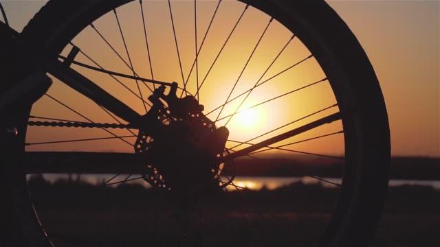 stockvideo's en b-roll-footage met sluit omhoog van fietswielen en vrouwelijke voetenschoenen die buiten stad in de lenteavond fietsen die milieu bij zonsondergang in langzame motie in langzame motie in langzame motie verzorgen - fiets