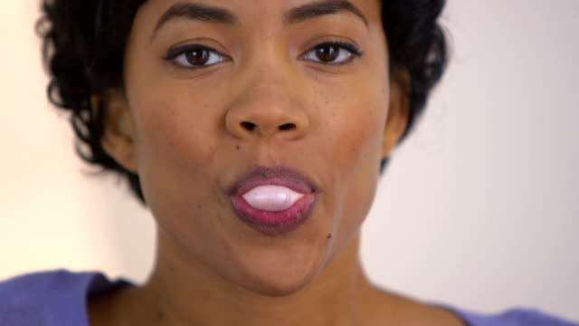 Close up of black woman trying to blow a bubble video