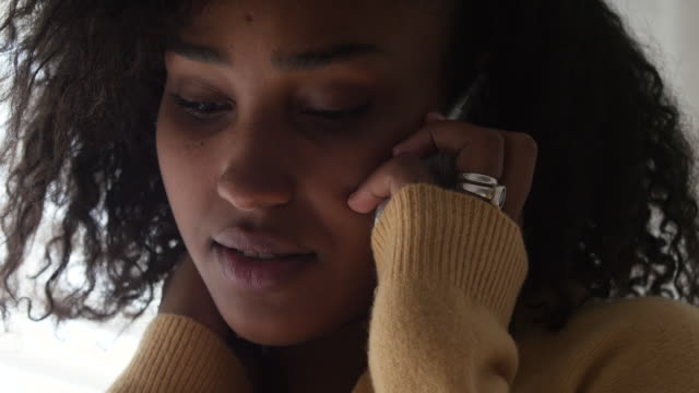 Close up of black young woman on a serious phone call using her smartphone Close up of black young woman on a serious phone call using her smartphone and looking very upset black people stock videos & royalty-free footage