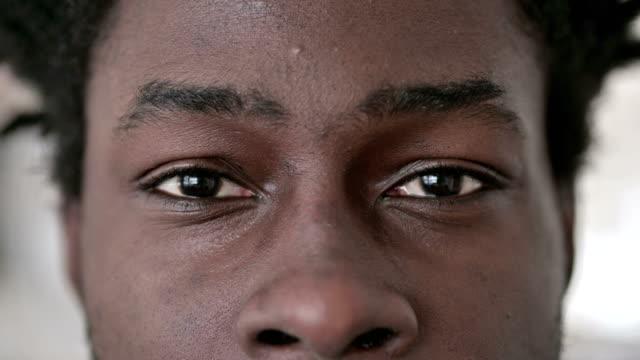 vidéos et rushes de fermez-vous vers le haut des yeux clignotants de l'homme africain - oeil