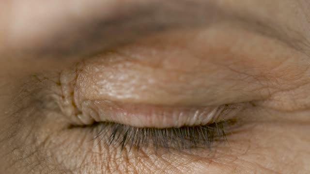 stockvideo's en b-roll-footage met close up van senior vrouw oog knippert - ooglid